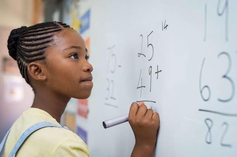 girl doing math problem on whiteboard