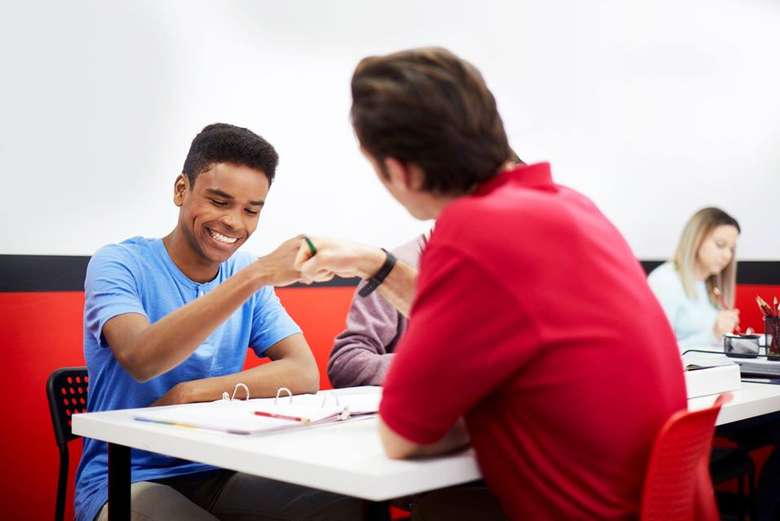 man in red shirt at table with male teen in blue shirt