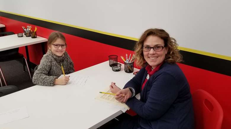 woman with glasses at table with young girl