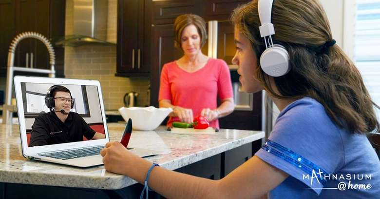 girl with headphones working with tutor over computer