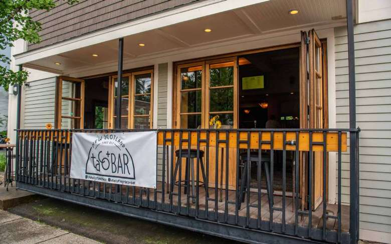 restaurant patio and white banner that reads new scotland taco bar