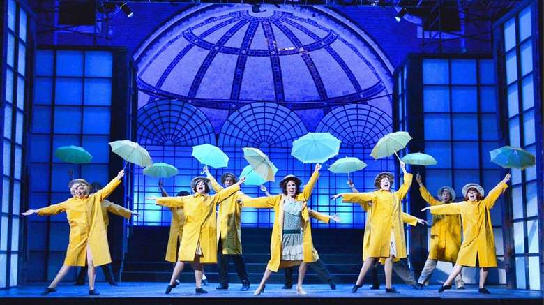 performers on stage with yellow raincoats and blue umbrellas