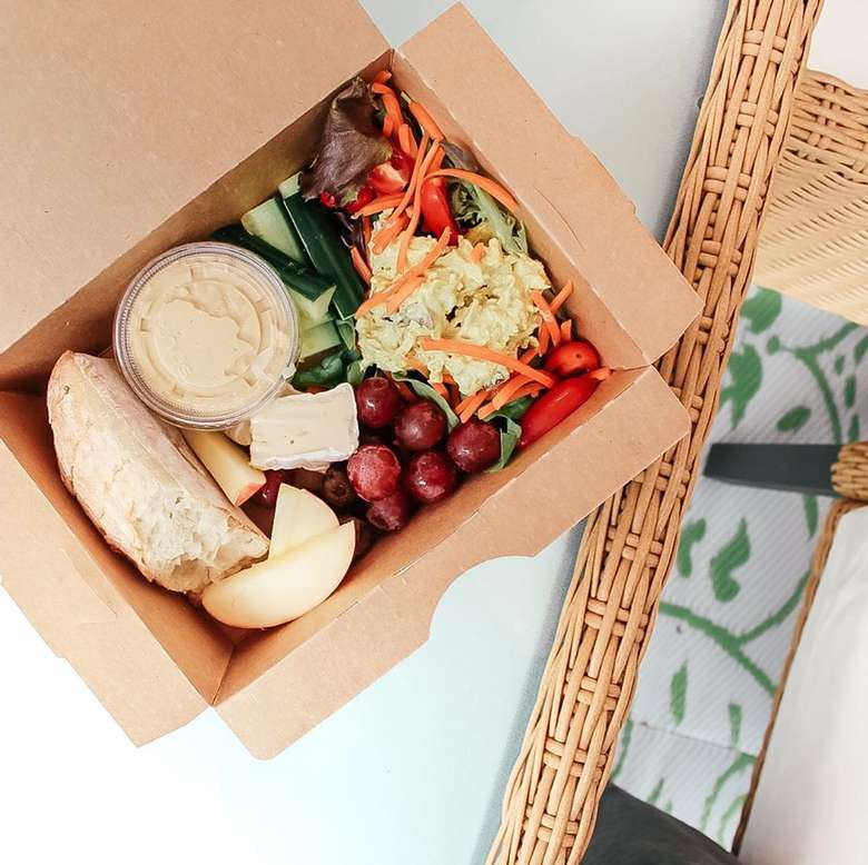 cardboard takeout box with salad and fruit
