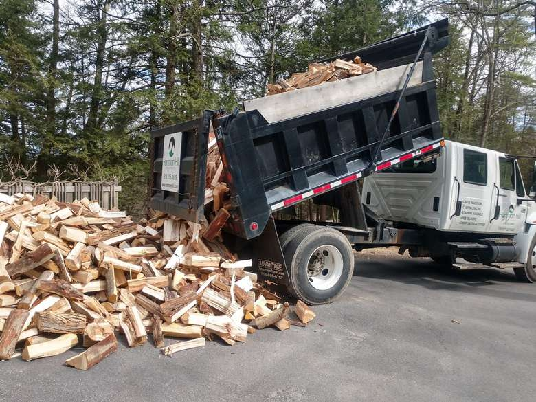 truck pouring firewood on ground