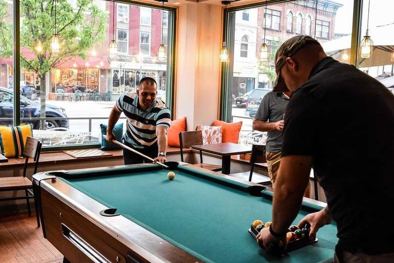 small group playing pool inside a restaurant