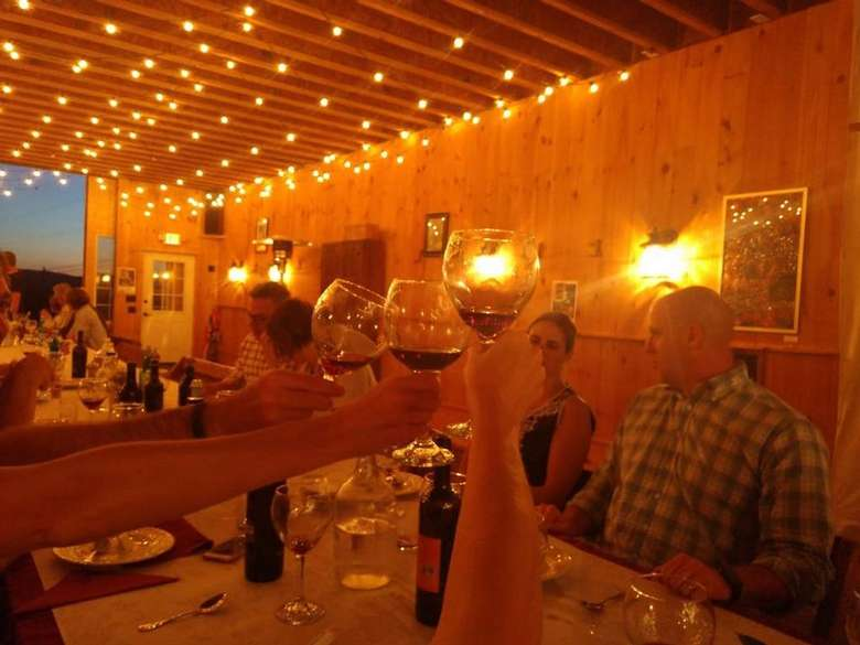 people inside a farm building at dinner table with lights around