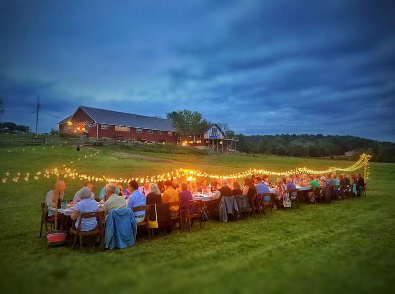 people dining at outdoor tables near a farm building