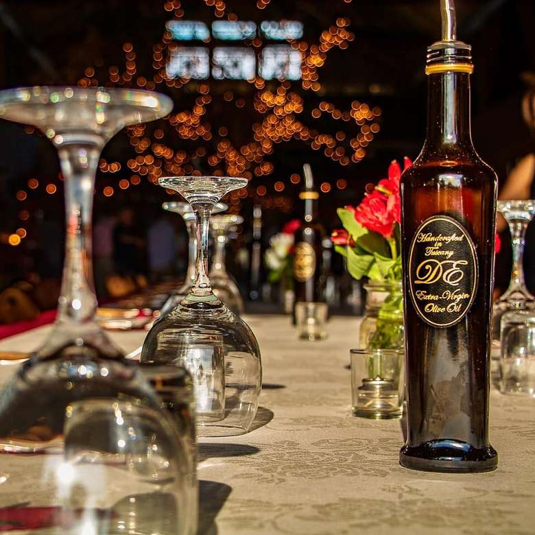 bottle of olive oil on table near upside down wine glasses