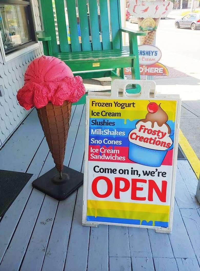 ice cream shop open sign with ice cream cone display near it