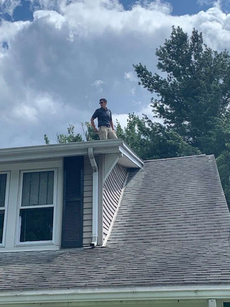 home inspector standing on a roof