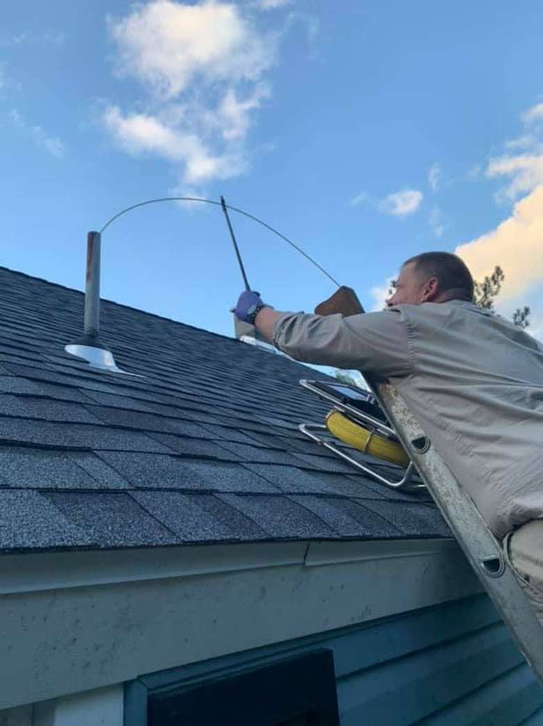 man on a ladder working near a roof