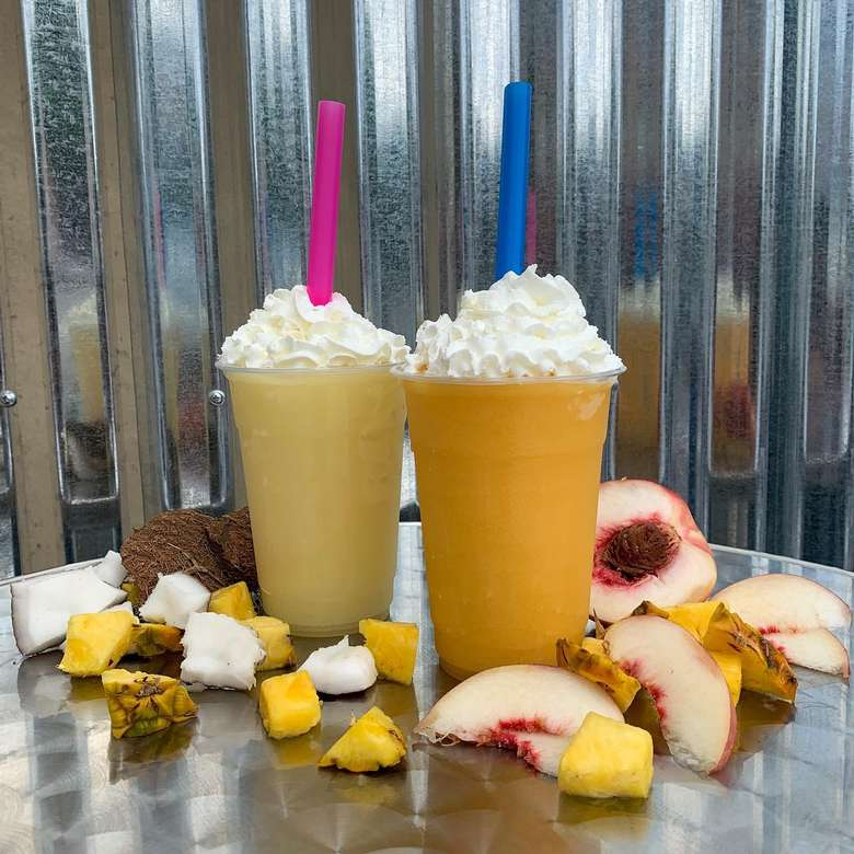 two pina colada slushies with whipped cream and straws