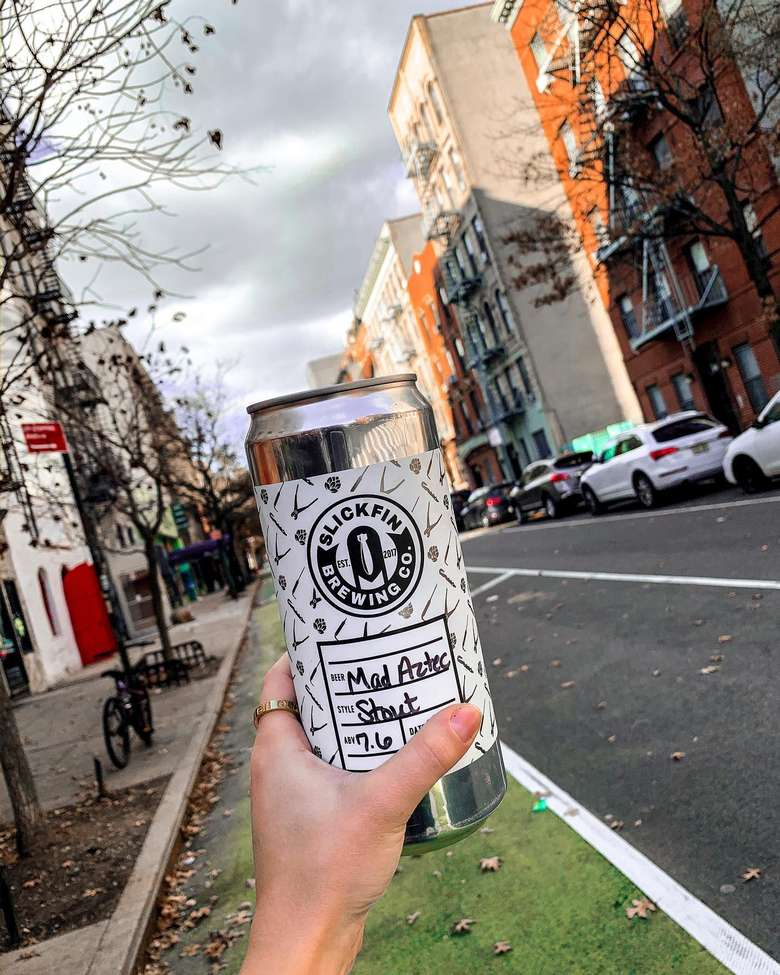person holding up a crowler with a street in the background