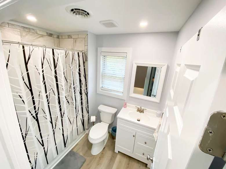 a bathroom with white walls, a white toilet, and a white sink