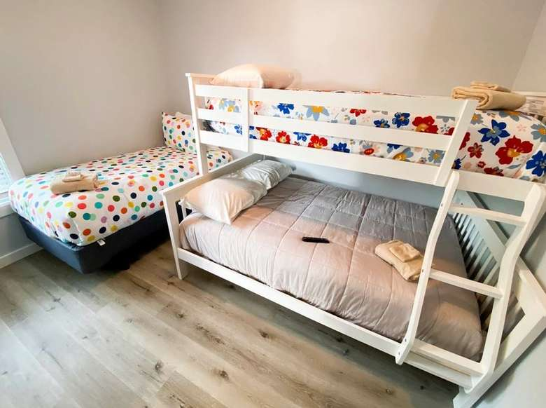 a bunk bed and a smaller bed next to it