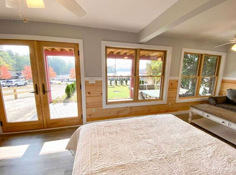 the end of a bed and a view of the outdoors through glass windows and doors