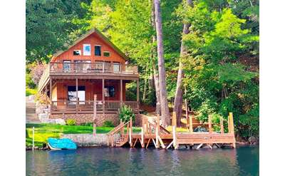 a two story home located by a lake shoreline