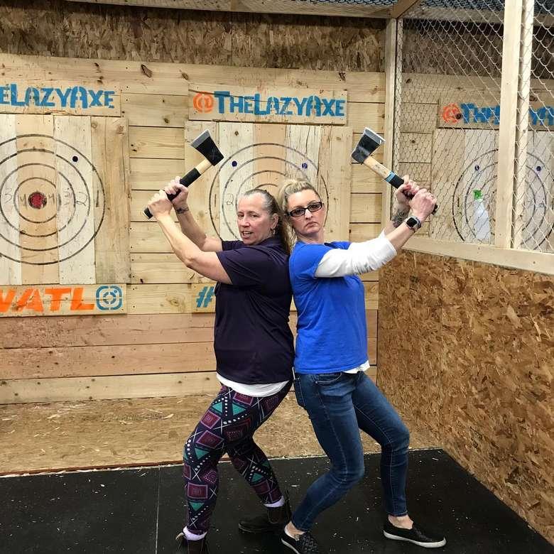 women posing at axe-throwing place