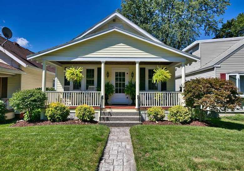 front of a yellow house with a stone walkway