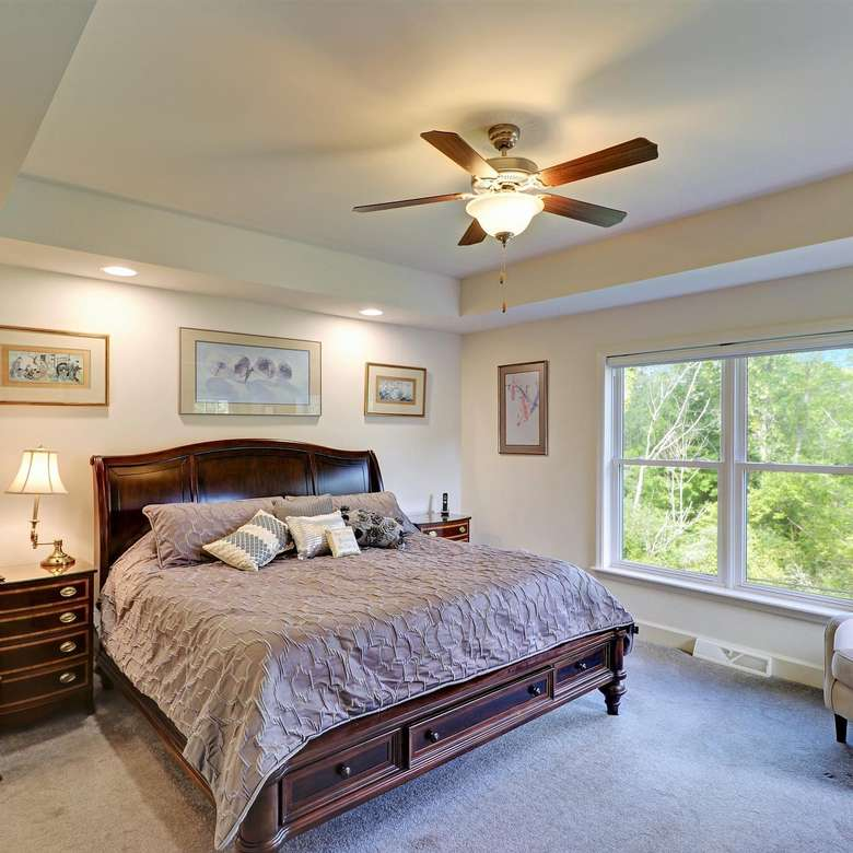 a bedroom with a bed, windows on one wall, and a ceiling fan light