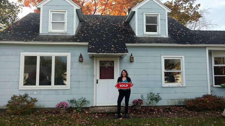woman standing in front of a blue house holding a sold sign.