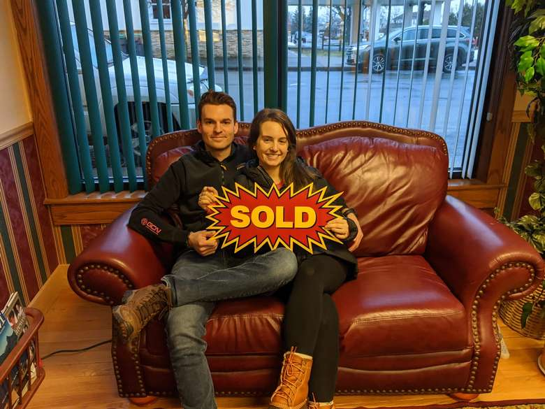 couple sitting on a couch with a sold sign.