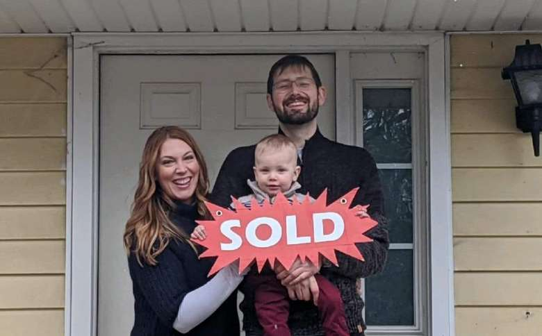Family holding a sold sign in front of a house.