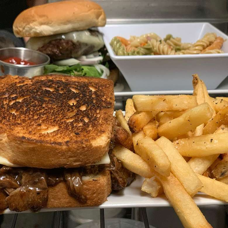 plates with fries, a sandwich, a burger, and pasta salad