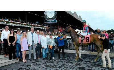 horse and its team in the winner's circle