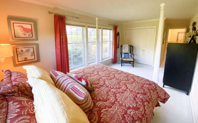 a bedroom with a closet, a black dresser, and a bed with red and white covers