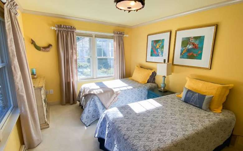 a bedroom with two beds side by side, yellow walls, and two paintings on the wall