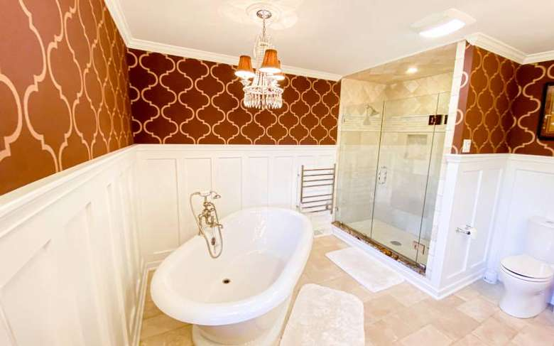 a large bathroom with a glass wall shower, a white toilet, and a white tub