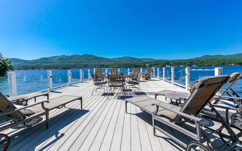 a sundeck on a lake with patio furniture on the top