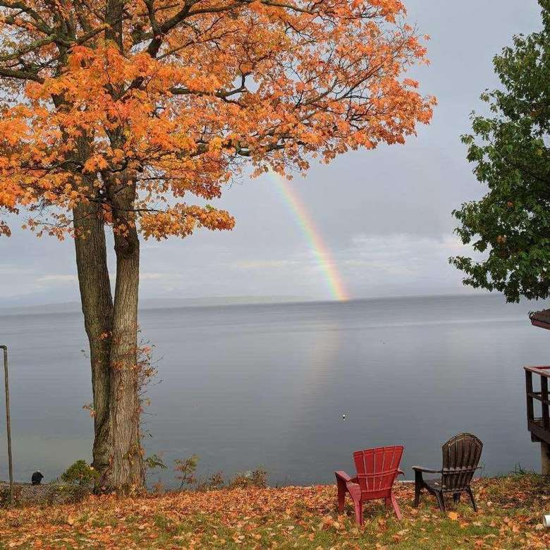 a rainbow in the sky over a lake
