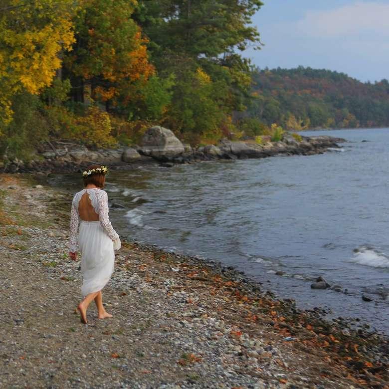 a woman in a wedding dress walking on a lake shoreline
