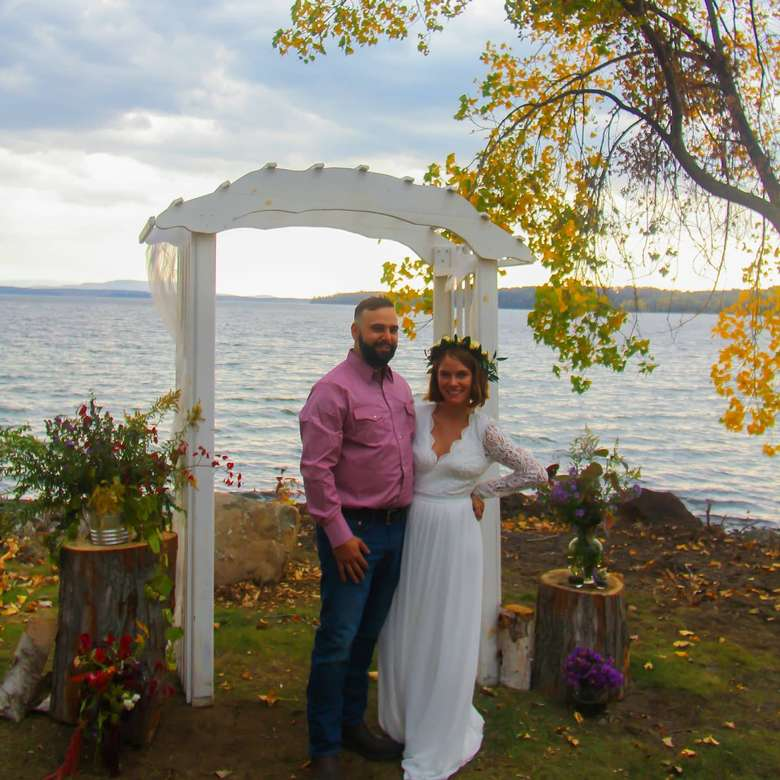 bride and groom standing near a wedding ceremony arch with a lake in the background