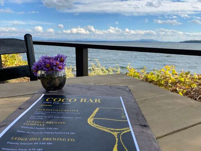 a menu on a table with a lake in the background