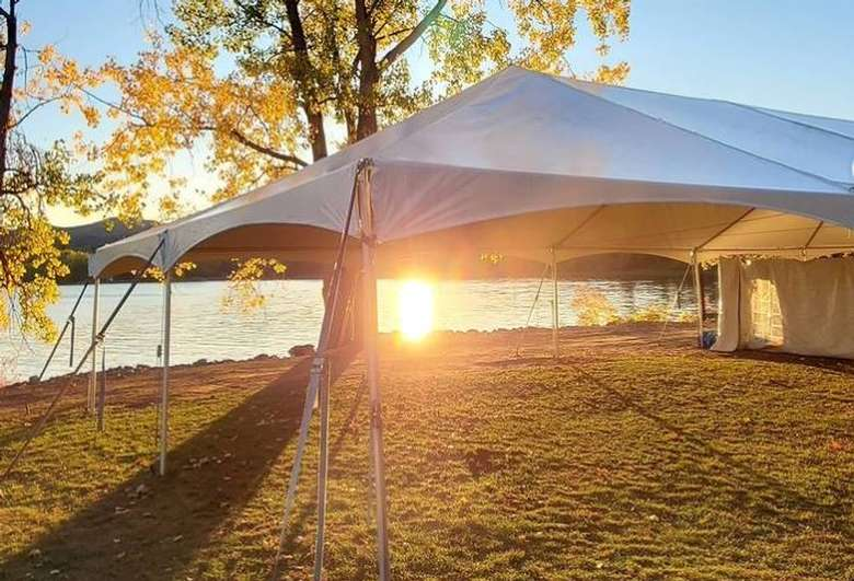 a white event tent set up outdoors by a lake