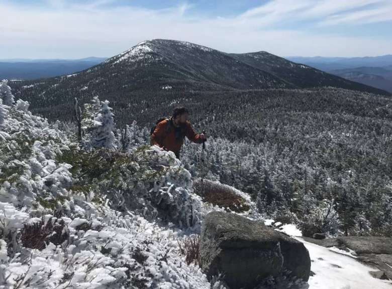 hiker walking on trail with view of snowy mountains and woods in the distance