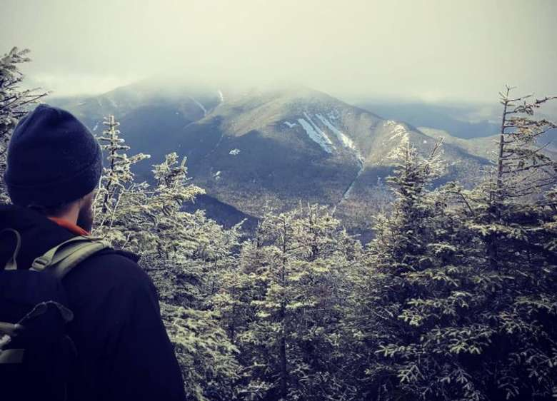 man looking out at snowy mountain