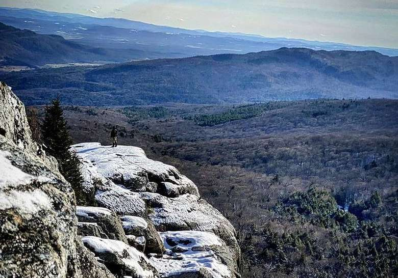 a far away view of a hiker on a rocky cliff looking into the distance