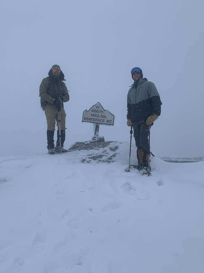 two men standing in snow near whiteface mountain sign