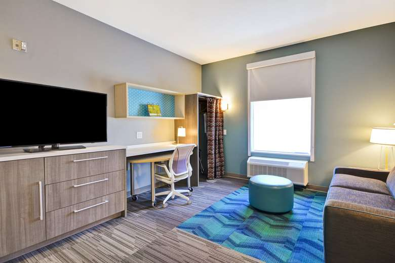 a work space in a suite with a desk, tv, and couch