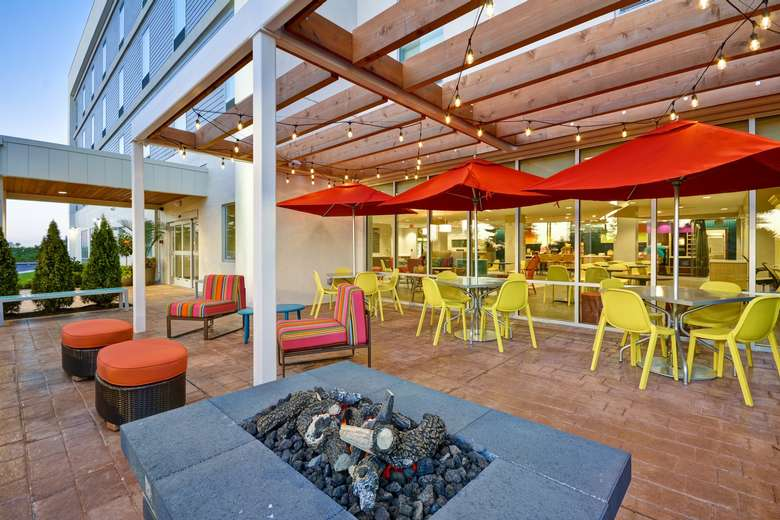 a patio area with chairs, tables, and a fire pit