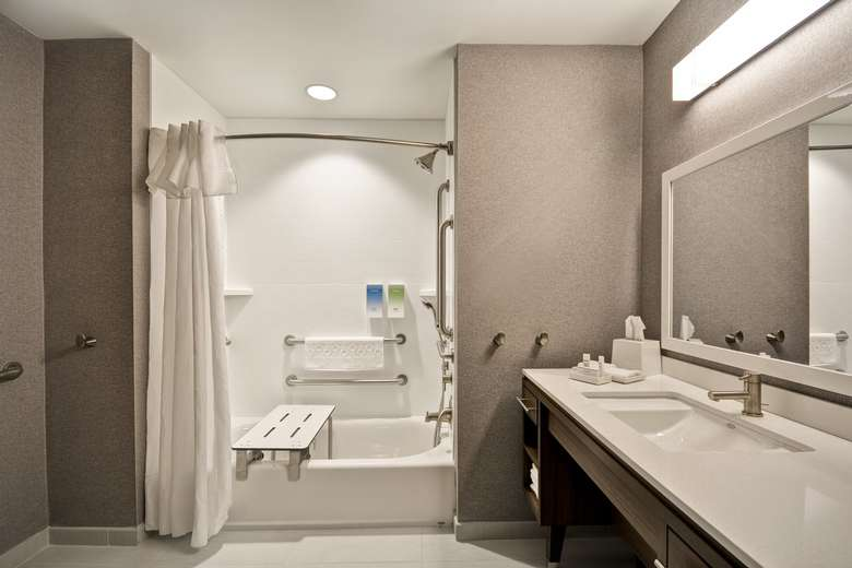 a hotel room bathroom with a tub and shower and a sink area