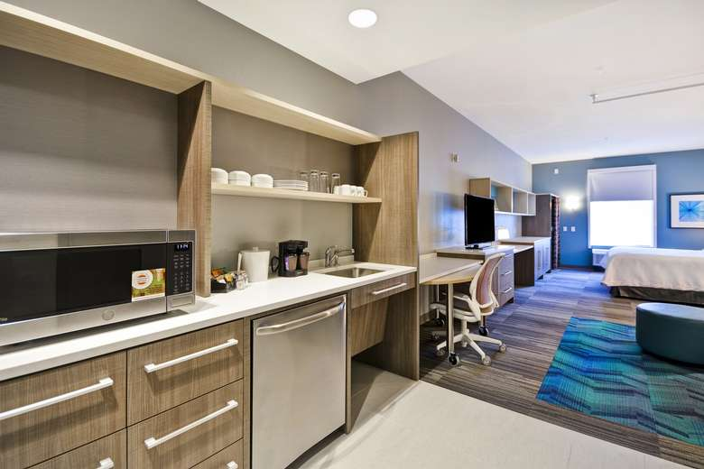 a kitchen area in a suite with a microwave, sink, and coffee maker