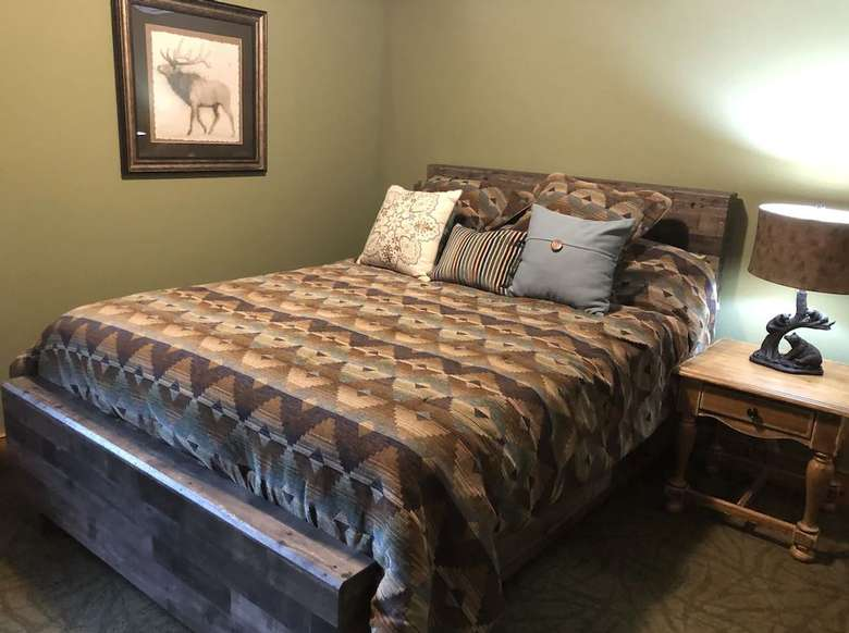 bedroom with bed, nightstand, and painting of moose on the wall