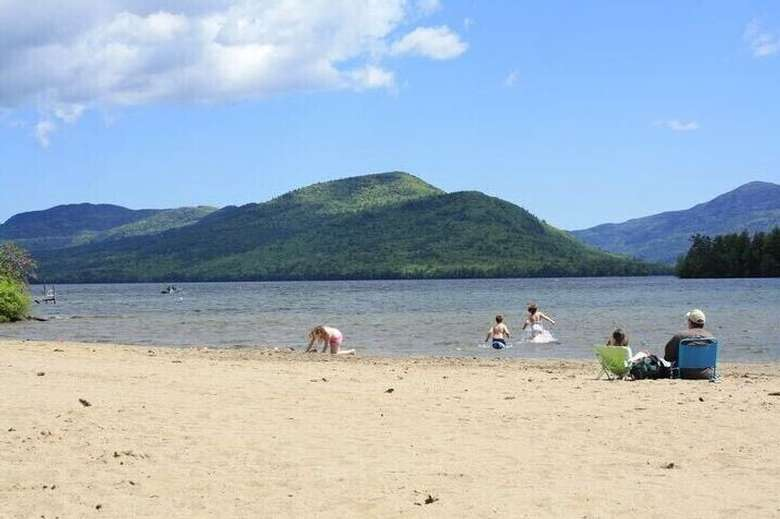 people at a beach with mountains in the distance
