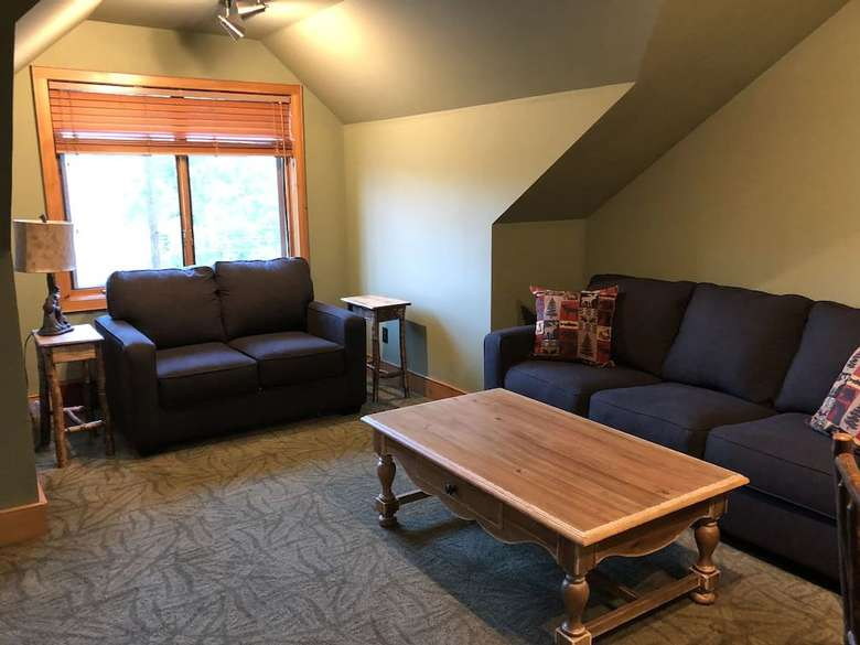 coffee table and two couches with a window on the back wall