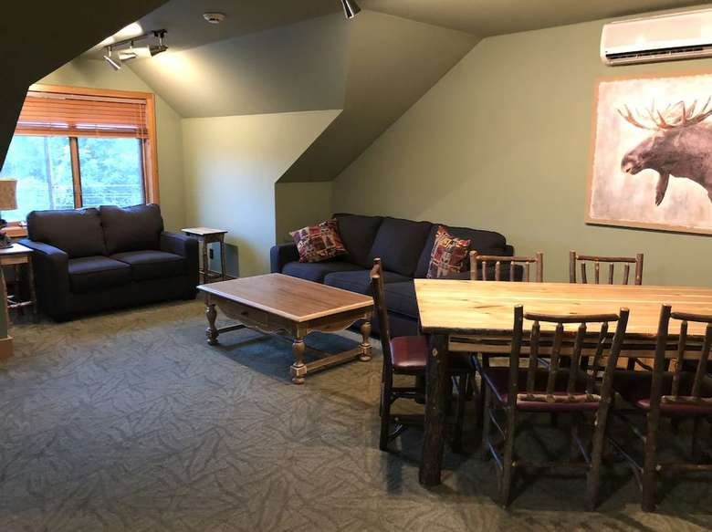 a living room and dining area with couches and a dinner table